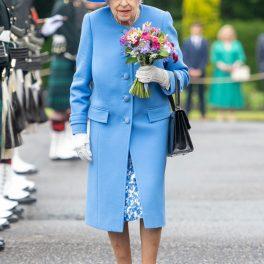 Regina Elisabeta într-un costum albastru și o pălărie de aceasși culoare în timp ce este întâmpinată în mod oficial la vizita sa din Scoția