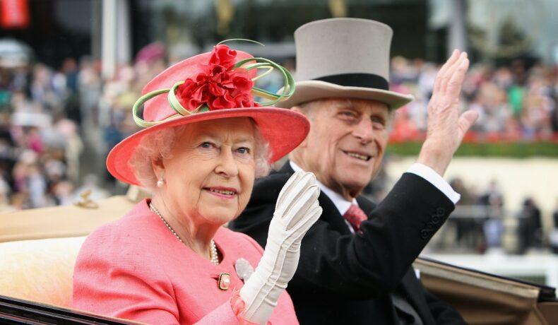 Regina Elisabeta într-un costum roz cu o pălîrie cu trandafir ăn timp ce face cu mâna publicului alături de Prințul Philip la costum care salută mulțimea la Ladies Day în Ascot în anul 2011