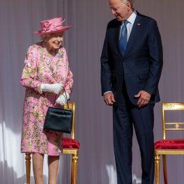 Regina Elisabeta într-o rochie roz cu imprimeu floral alături de Președintele statelor Unite ale Americii, Joe Biden, îmbrăcat la costum, la întâlnirea lor oficială de la castelul Windsor