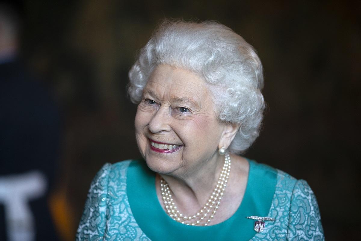 Portret al Reginei elisabeta îmbrăcată într-o rochie albastră în timp ce zâmbește la o recepție oficială din 2018 de la palatul din Edinburgh, Holyroodhouse