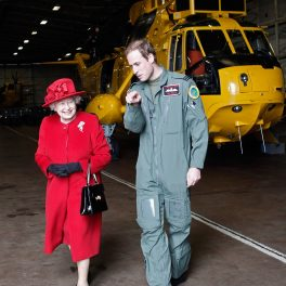 Regina Elisabeta îmbrăcată într-un costum roșu și purtând o pălărie de aceeasși culoare în timp ce merge alături de nepotul său, Prințul William care poartă un costum de militar