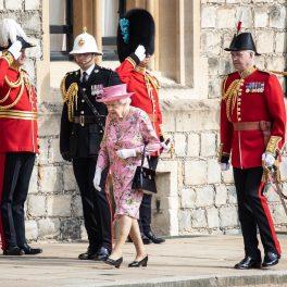 Regina Elisabeta în rochie roz cu imprimeu floral în timp ce emrge însoțită de garda Regală la întâlnirea cu Președintele Joe Biden de la Castelul Windsor