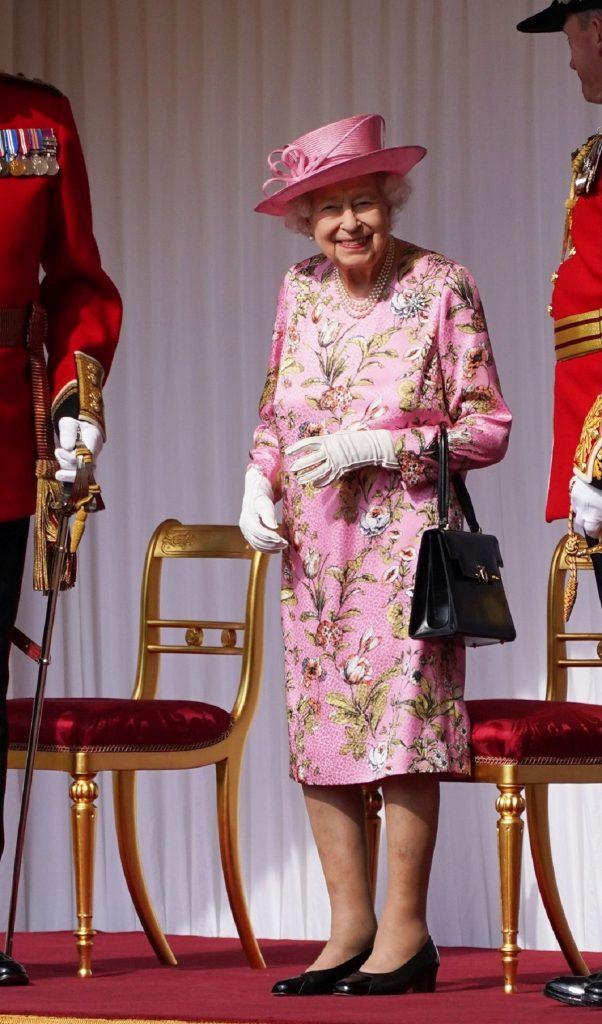 Regina Elisabeta i-a adus un tribut strănepoatei sale și a îmbrăcat o rochie roz cu imprimeu floral și o pălărie de aceeași culoare în timp ce ține în mână o poșetă neagră și zâmbește la cameră înainte să se întâlnească cu Președintele Biden