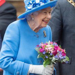 Regina Elisabeta purtând un costum albastru și o pălărie în timp ce merge la vizita unei fabrici de suc din Scoția