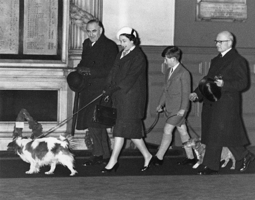Regina Elisabeta însărcinată cu Prințul Andrew alături de fiul său Prințul Charles și alți doi bărbați în timp ce își plimbau câinii după o vizită de Crăciun