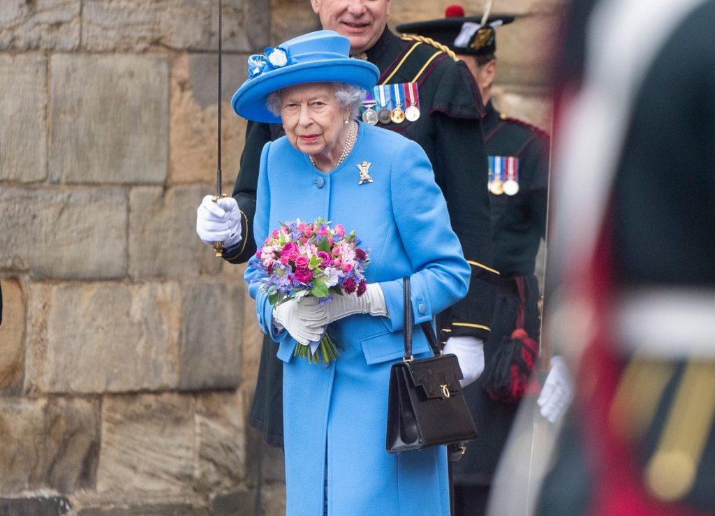Regina Elisabeta purtând un costum albastru în timp ce ține în mână un buchet de flori la vizita sa oficială de la o fabrică de suc din Scoția