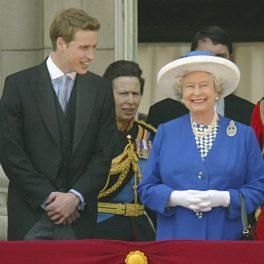 Prințul William la costum negru alături de Regina Elisabeta îmbrăcată în costum albastru și purtând mănuși și pălărie albă în timp ce privesc de la balcon ceremonia Trooping the Colour din 2003