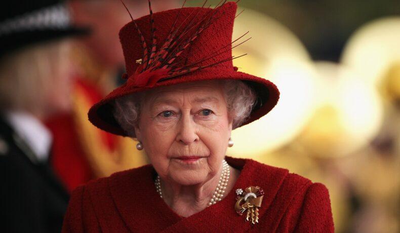 Portret al Reginei Elisabeta purtând un costum roșu și o pălărie elegantă roșie la reședința din Windsor unde s-a întâlnit cu Emirul Qatarului în 2010