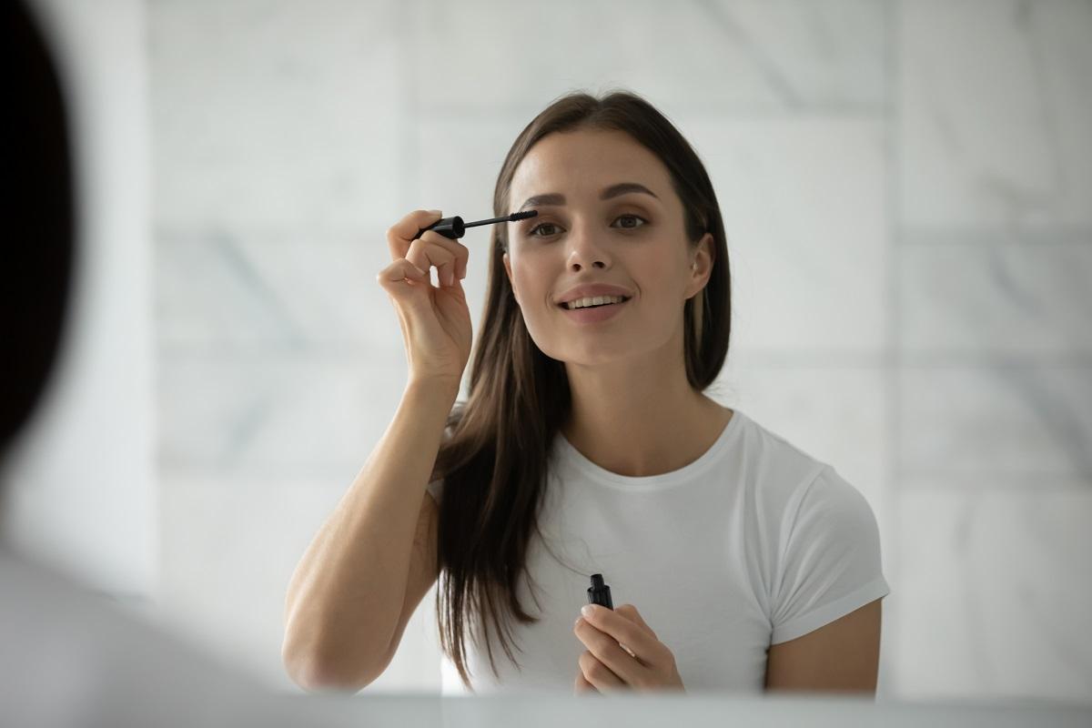 O tânără frumoasă înbrăcată în tricou alb care este la baie în fașa oblinzii și folosește rimelul rezistent la apă