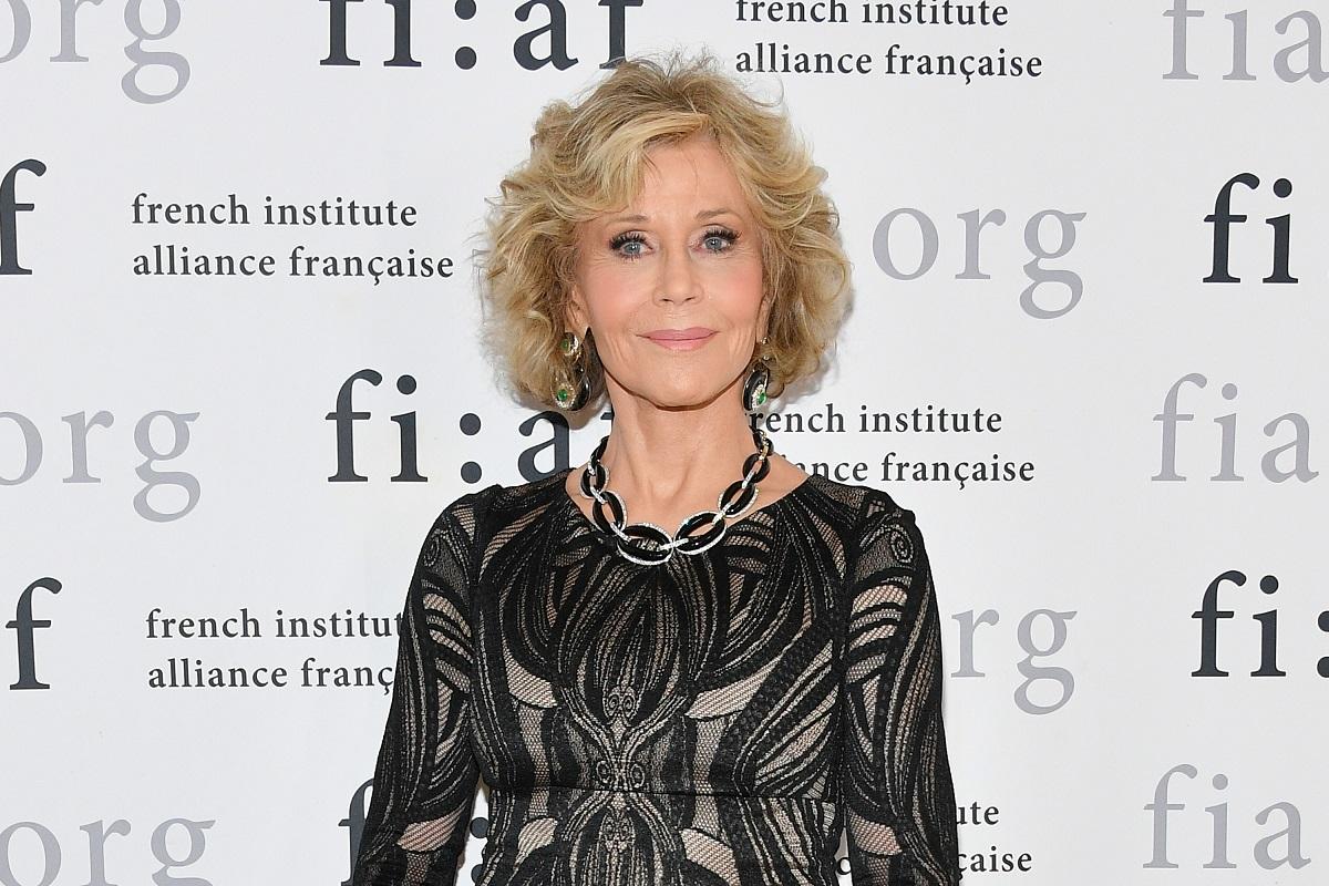 Portret al actriței Jane Fonda îmbrăcată într-o rochie neagră în timp ce zâmbește la camere și stă în spatele unui panou publicitar la Gala Trophee des Arts din New York din 2018