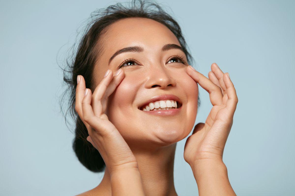O femeie care zâmbește, în timp ce-și atinge tenul cu degetele