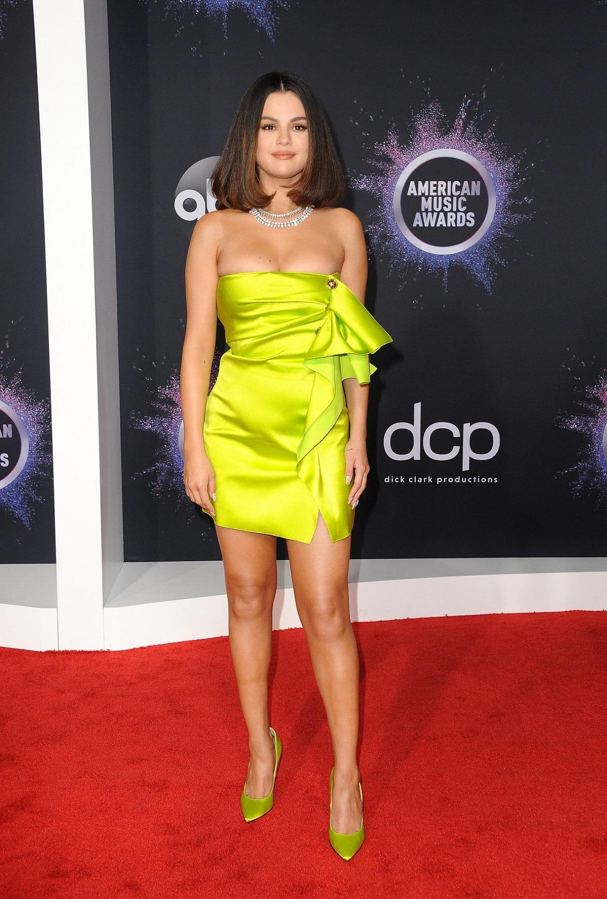 Selena Gomez pe covorul roșu cu părul tuns bob lung și purtând o rochie scurtă în culoarea muștarului la care a asortat o pereche de tocuri la Gala American Music Awards din 2019