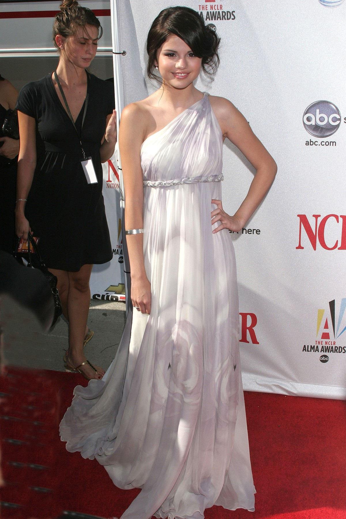 Selena Gomez cu părul strâns într-un coc și purtând o rochie albă vaporoasă dezvăluie secretul unei ținute perfecte pe covorul roșu în cadrul Premiilor ALMA care s-au derulat în 2008