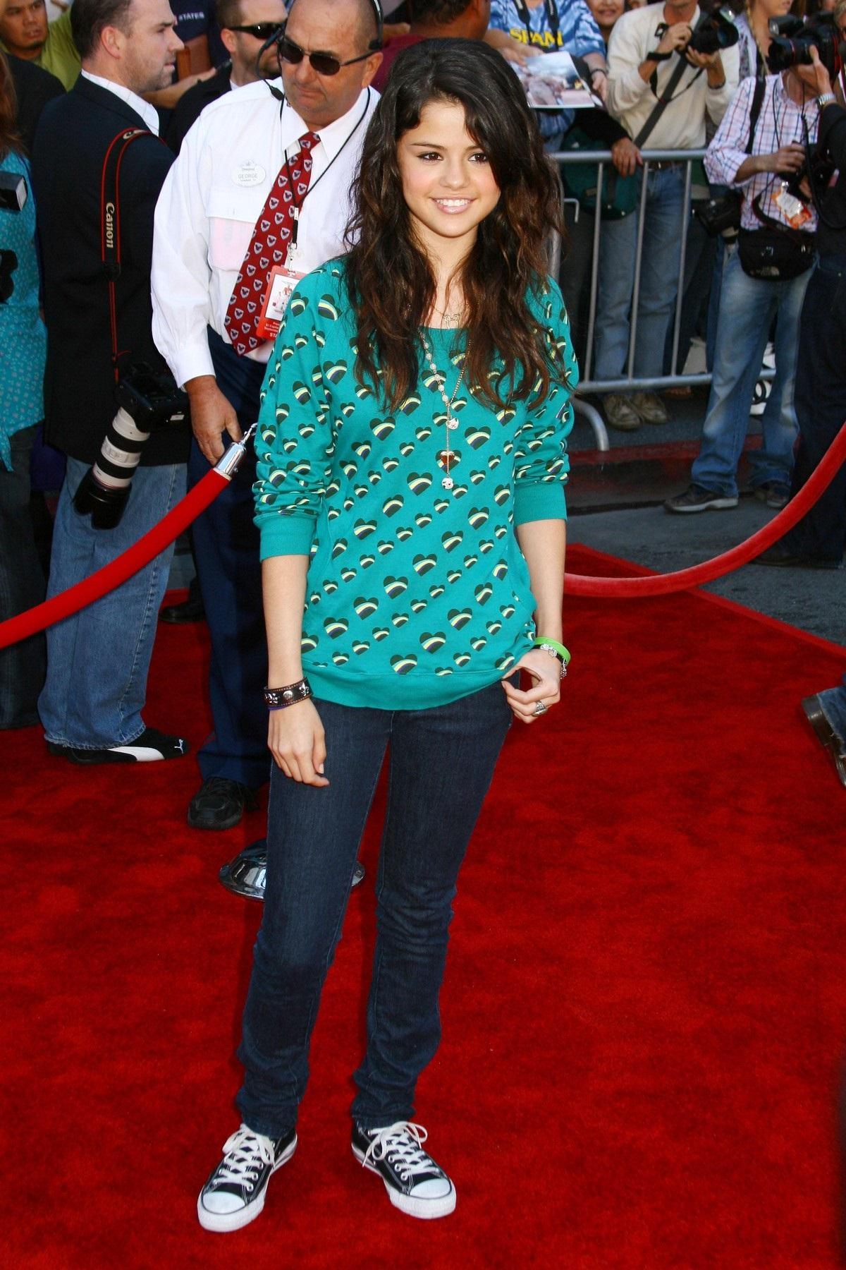 Selena Gomez în adolescență purtând o bluză lungă albastru deschis și o pereche de blugi în timp ce se află pe covorul roșu la premiera The Game Plan ce a avut loc în Los Angeles în 2007