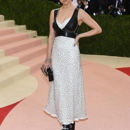 Selena Gomez cu părul prins într-o coadă în timp ce poartă o rochie albă cu buline mărunte negre peste care are un corset de piele și la care a asortat o pereche de cizme cu tocuri negre la Gala Muzeului Metropolitan de Artă din New York în 2016
