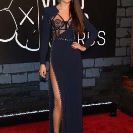 Selena Gomez într-o rochie semnată de Versace de culoare albastru închis în timp ce se află pe covorul roșu cu părul lung dat într-o parte privind cameramanii la Gala MTV Video Muzic Awards de la New York din 2013