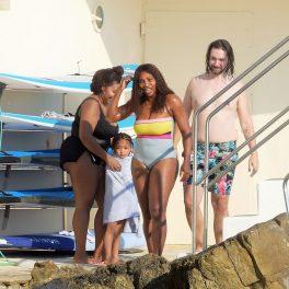 Serena Williams în costum de baie cu părul ud, alături de soțul ei proaspăt ieșit din piscină, Alexis și fiica lor Olympia care este înfășurată într-un prosop alb de către prietena lor de familie
