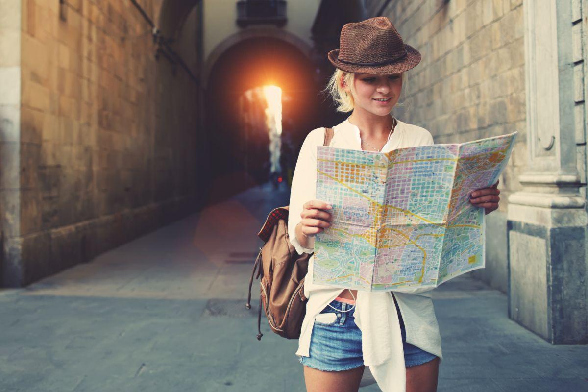 O turistă care încearcă să descopere următorul obiectiv, analizând harta geografică