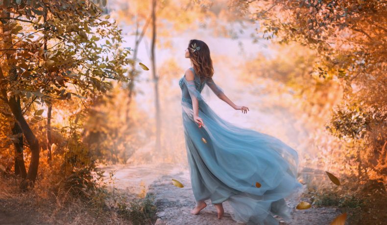 O femeie frumoasă care stă cu spatele într-o pădure și poartă o rochie albastră în timp ce o briză o ridică pentru a reprezenta zodiile de aer