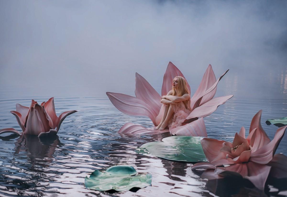Un lac liniștit învăluit de ceață pe care se află trei flori roz de nufăr, iar în interiorul acestora stă o femeie frumoasă care reprezintă zodiile de apă și liniștea acestora