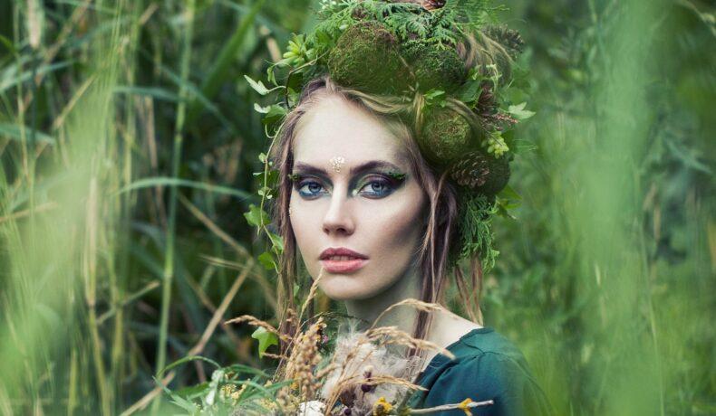 O femeie frumoasă cu machiaj de zână care stă în iarbă și în păr are diferite flori, conuri și crenguțe pentru a reprezenta una din zodiile de pământ
