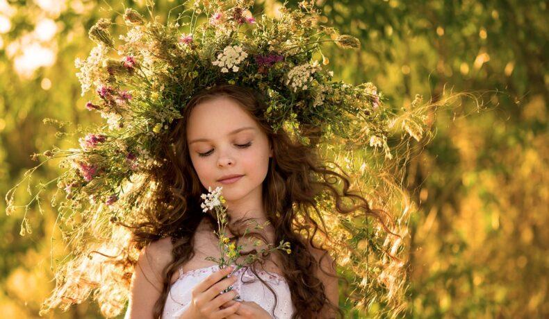 O fetiță cu părul încununat de flori colorate care ține în mână o margaretă și o privește atent în timp ce ia parte la unele tradiții de Sânziene din România