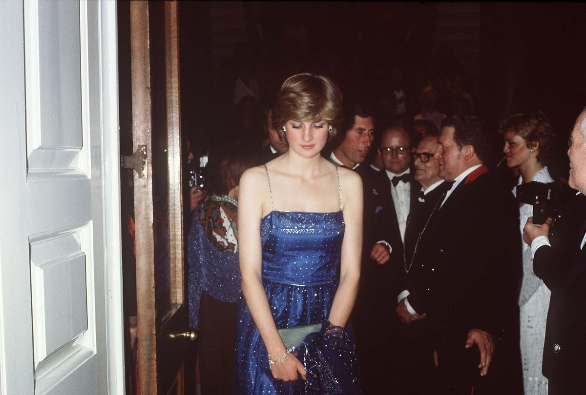 Prințesa Diana purtând o rochie albastră cu paiete în timp ce pășește afară dintr-o încăpere de la un eveniment oficial