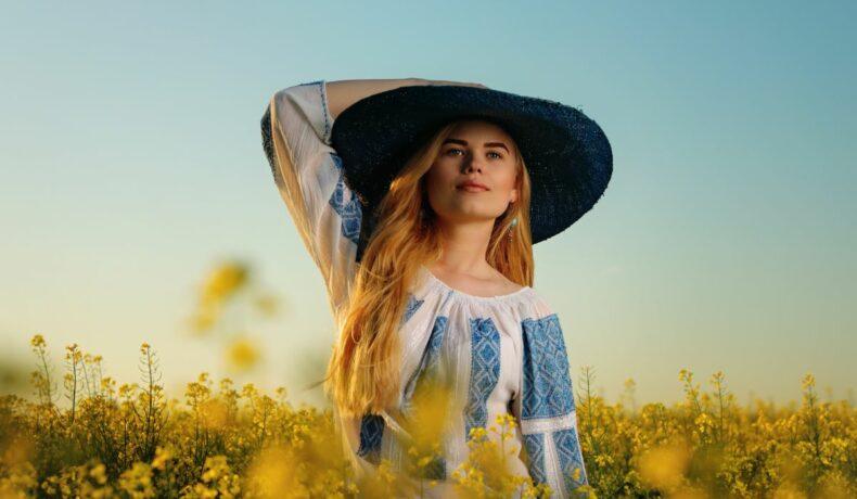 O femeie tănără care poartă ie și pălărie largă, în mijlocul unui câmp de rapiță