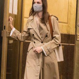Angelina Jolie, în timp ce iese dintr-un bloc, cu mâna pe ușă, fără agenți de securitate, în New York, clădire în care locuiește Johnny Miller