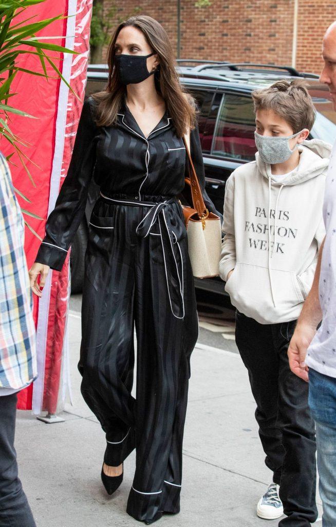Angelina Jolie poartă o rochie neagră de satin, împreună cu fiul ei KNox, ce este îmbrăcat într-un hanorac alb