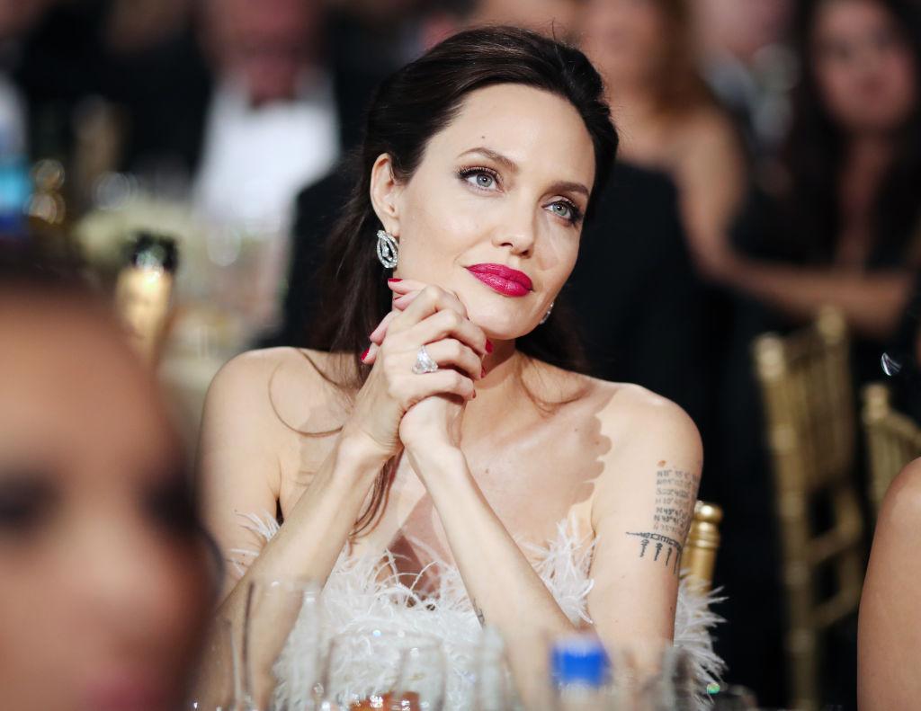 Angelina Jolie, la masă, la Critics' Choice Awards, în 2018, în timp ce ascultă un discurs