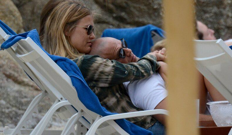 Bar Refaeli, alături de soț, pe șezlong, la plajă, în timp ce stau îmbrățișați