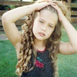Bar Refaeli,, imagine din copilărie, cu părul lung și ondulat, în timp ce pozează la cameră