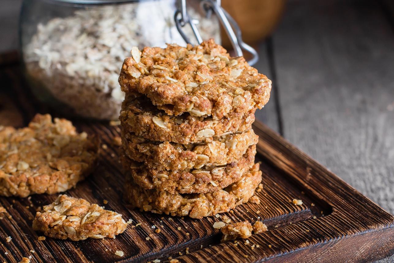Biscuiți cu fulgi de ovăz și miere de albine pe un suport de lemn