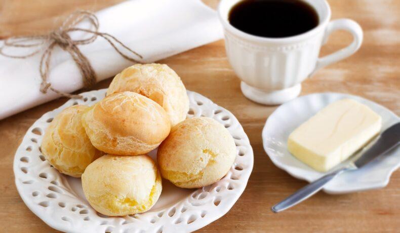 Chifle pufoase cu ricotta, pe o farfurie albă, alături de o ceașcă cu cafea