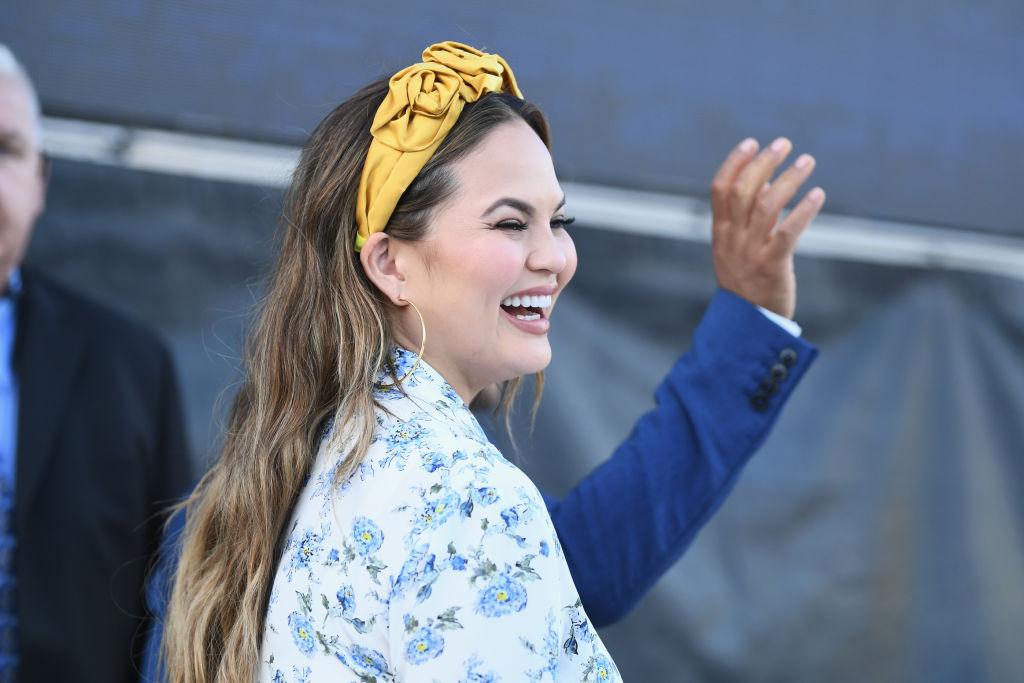 Chrissy Teigen, la un eveniment caritabil, în 2018, în timp ce râde la fotografi