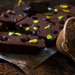 Ciocolată de casă cu fistic și merișoare, porționată pe un suport