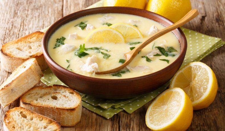 Ciorba de pui á grec, așezată într-un bol din ceramică, cu o ligură din lemn în ea, alături de bucăți de lămâie și pâine prăjită.
