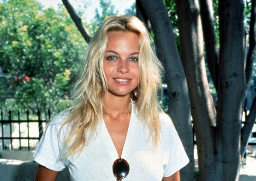 Pamela Anderson avea un look mai natural în tinerețe, optând pentru tricouri. În imagine are un tricou alb, părul lung, ochelari de soare prinși de bluză