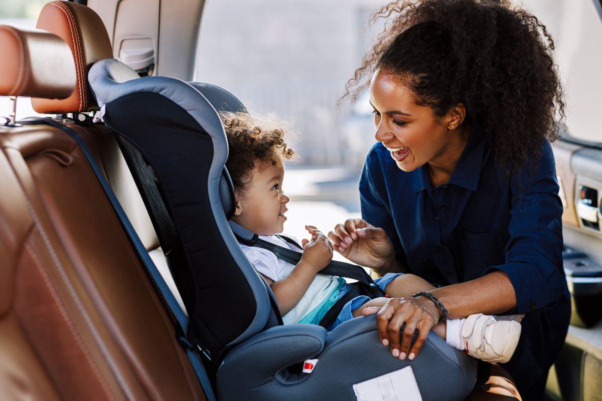 Mamă zâmbitoare învață cum să instaleze corect scaunul auto pentru copilul său, cu părul creț.