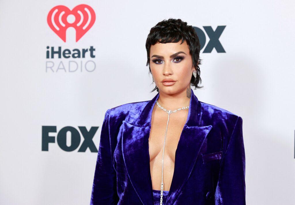 Demi Lovato aparut într-un costum albastru dupa ce a dezvaluit ca e non-binara, cu decolteu, fundal alb, la evenimentul iHeartRadio Music Awards din mai 2021