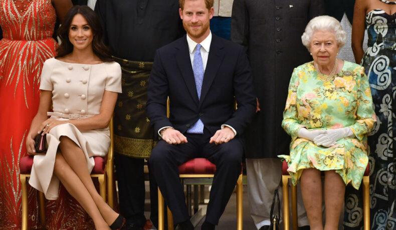 Ducii de Sussex, alături de Regina Elisabeta a II-a, la o ceremonie de premiere, îmbrăcați elegant, pe scaune, în 2018