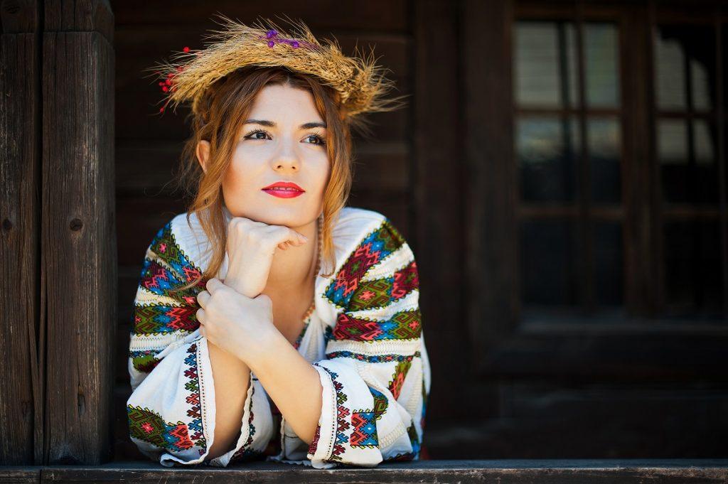Portret al unei femei frumoase care stă pe prispa unei case cu mâinile sub bărbie în timp ce privește în zare