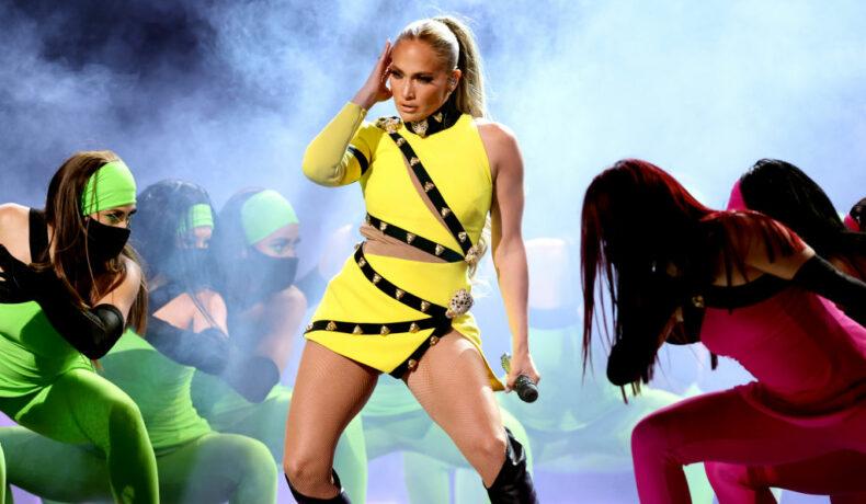 Jennifer Lopez, în concert, pe scena VAX Live, alături de dansatorii ei, într-o ținută galbenă