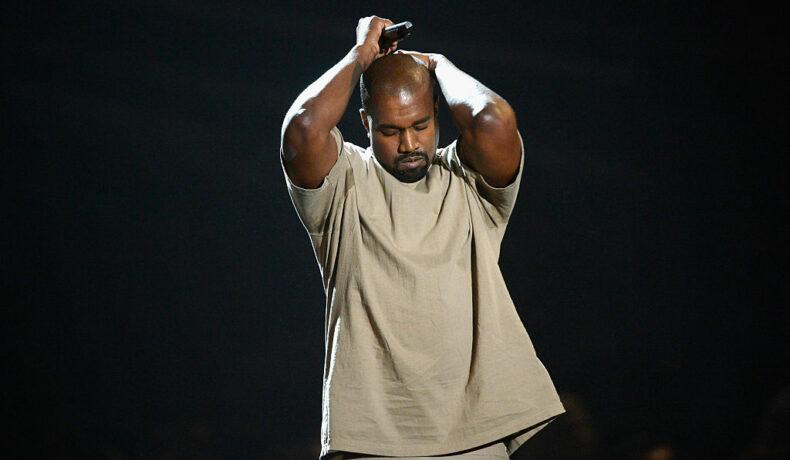 Kanye West, pe scenă, la MTV Video Music Awards, în 2015, cu mâinile în cap