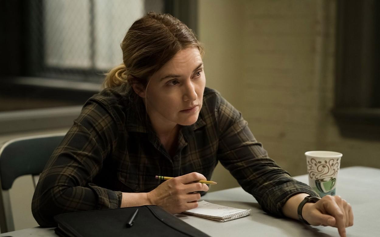 Kate Winslet, la masă, în timp ce scrie, o imagine din filmul Mare of East