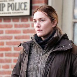 Kate Winslet, îmbrăcată în haine groase, cu privirea pierdută, în rolul lui Marianne, detectivul din producția Mare of Easttown