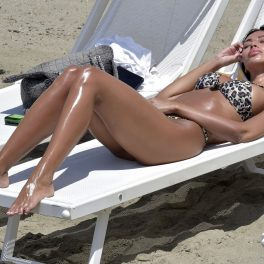 Mădălina Ghenea, îmbrăcată cu un costum de baie cu imprimeu de leopard, în timp ce stă la plajă