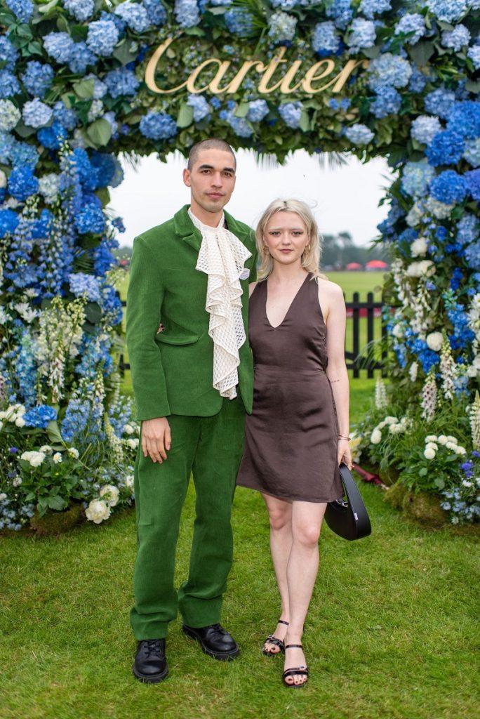 Maisie Williams și-a schimbat look-ul, reuben selby, schimbare look, eveniment cup polo, ea in rochie mao, el in costum verde, fundal cu verde si albastru