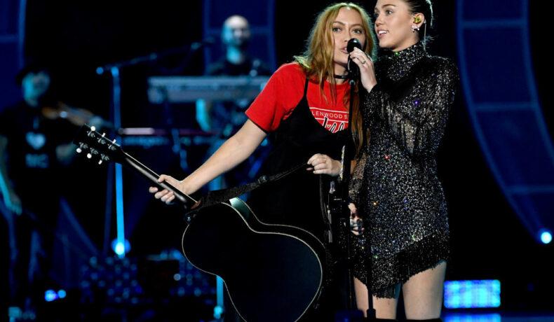 Miley, pe scenă, alături de sora sa, Brandi, la iHeartRadio Music Festival